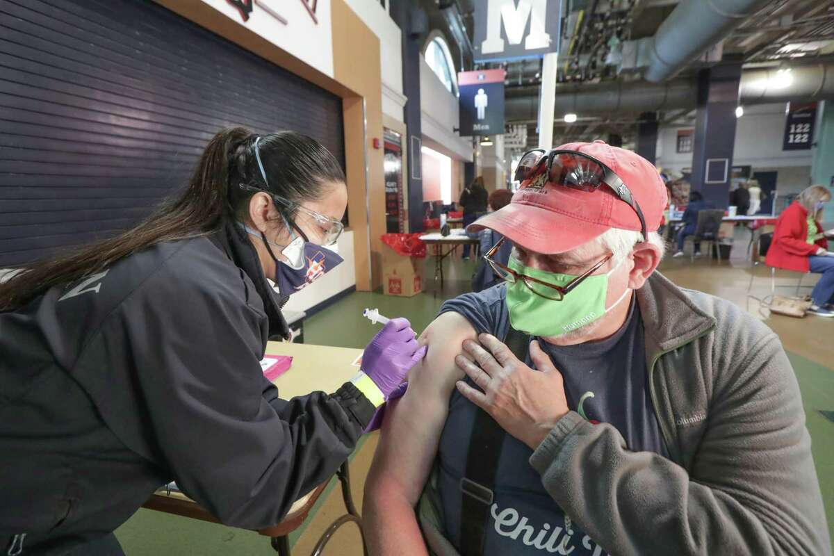 Houston Fire Department Paramedic Crystal Ortiz gives Robert Moore his COVID-19 vaccine at Minute Maid Park Saturday, Jan. 9, 2021, in Houston.