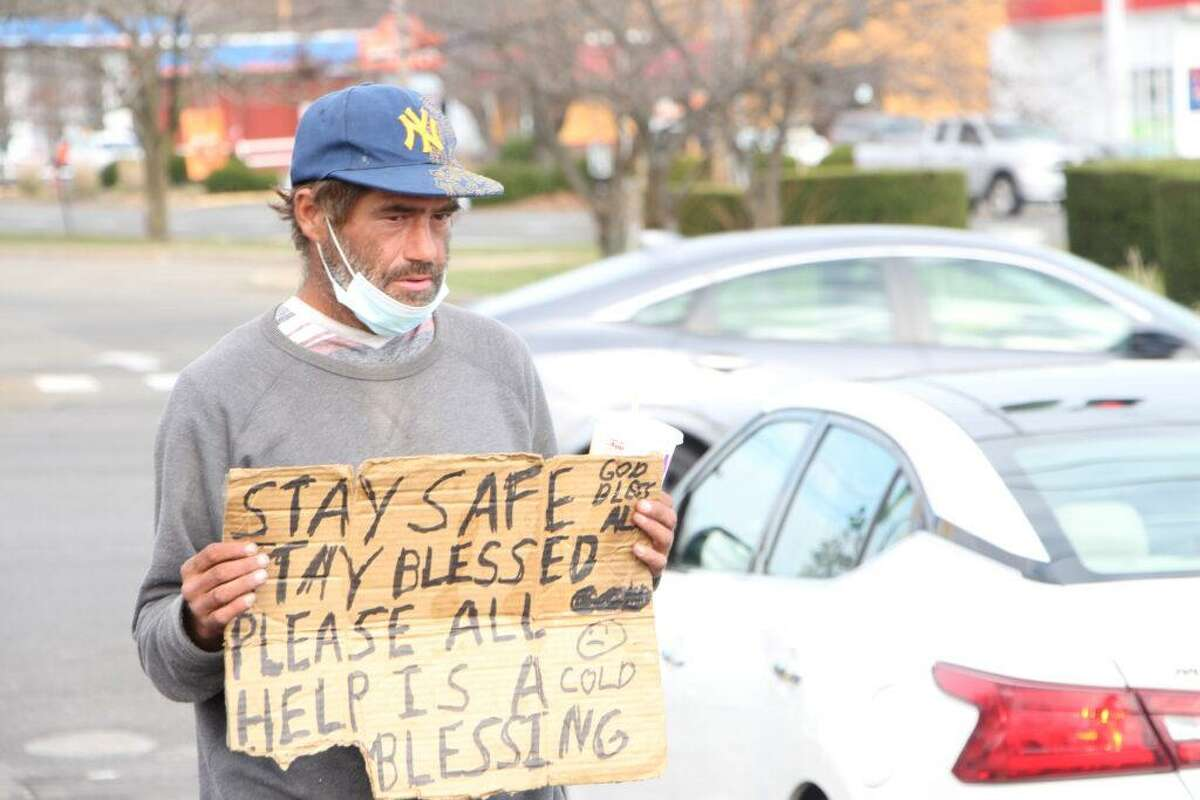 John Kennedy, 40, stands in the parking lot of the Hamden Mart shopping mall on Dixwell Avenue on Saturday, Nov. 21. Kennedy chose this spot to panhandle because it is located near a bank and other essential businesses.