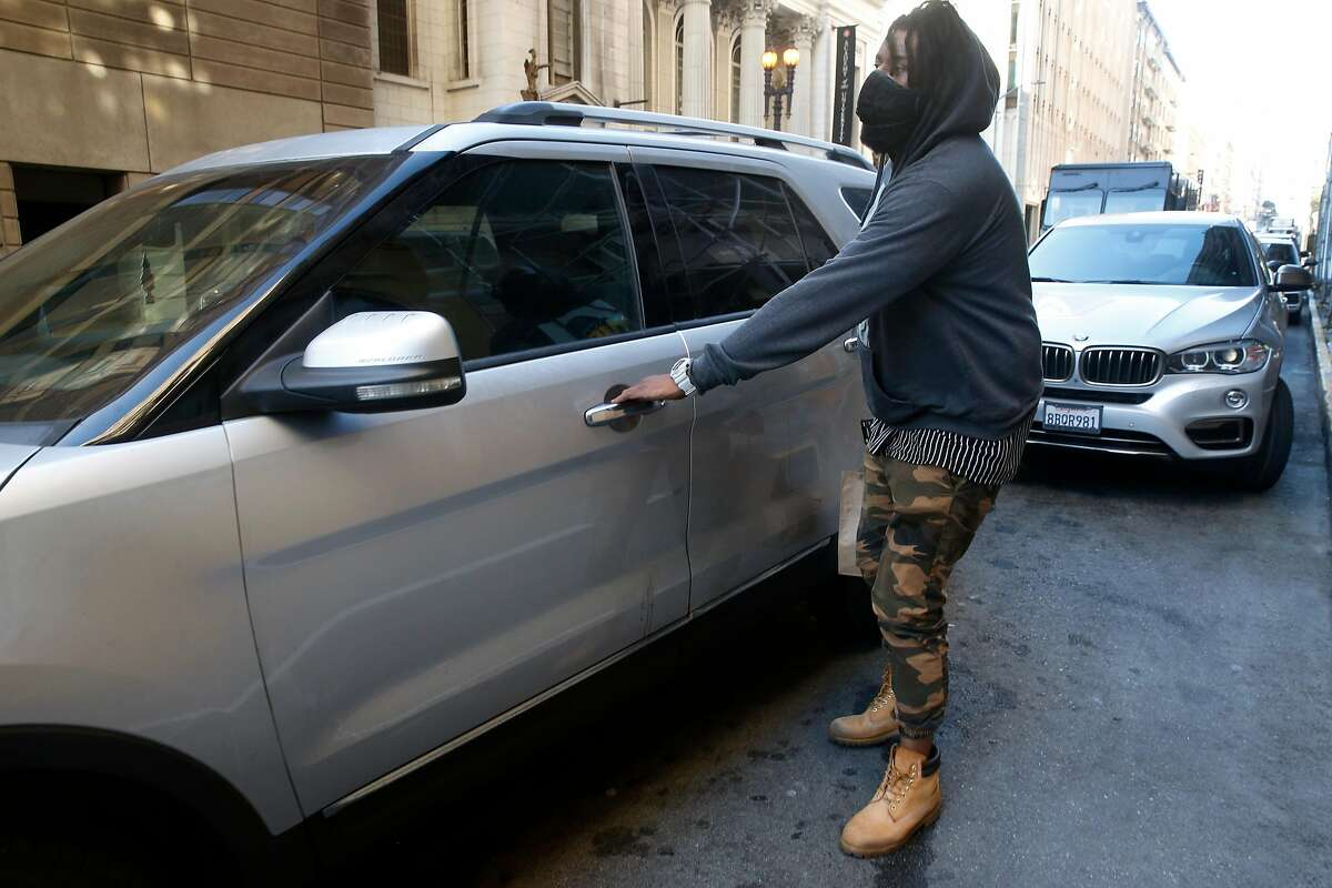 """DoorDash driver Gleyson Coelho climbs into his car after picking up an order for delivery at Cafe Encore on Post Street in San Francisco, Calif. on Wednesday, Nov. 4, 2020. California's strict """"ABC test"""" that makes it hard to claim workers are independent contractors applies retroactively, the state Supreme Court ruled on Thursday in a decision that could hurt Uber, Lyft and other gig companies in numerous lawsuits."""