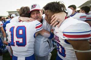 Austin Westlake head coach Todd Dodge embraces Luke Nicklos (19) and Zane Minors after Westlake beat North Shore 24-21 in the Class 6A Division I semifinal playoff high school football game at Legacy Stadium Saturday, Jan. 9, 2021 in Katy, Texas.