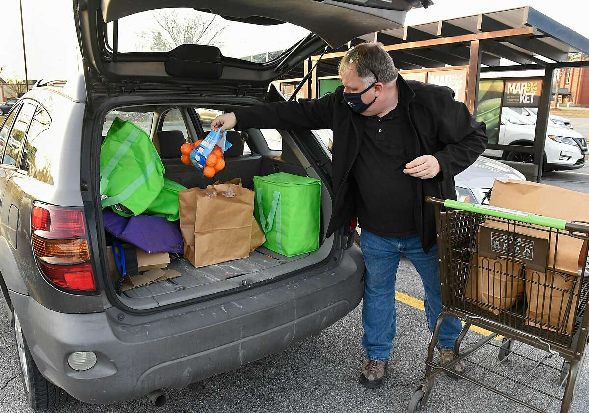 Instacart shopper Roger Allan of Hadley, N.Y. loads a customer's groceries in his car in December after shopping. The company is offering its non-employee workers $25 for their time if they get a coronavirus vaccination.