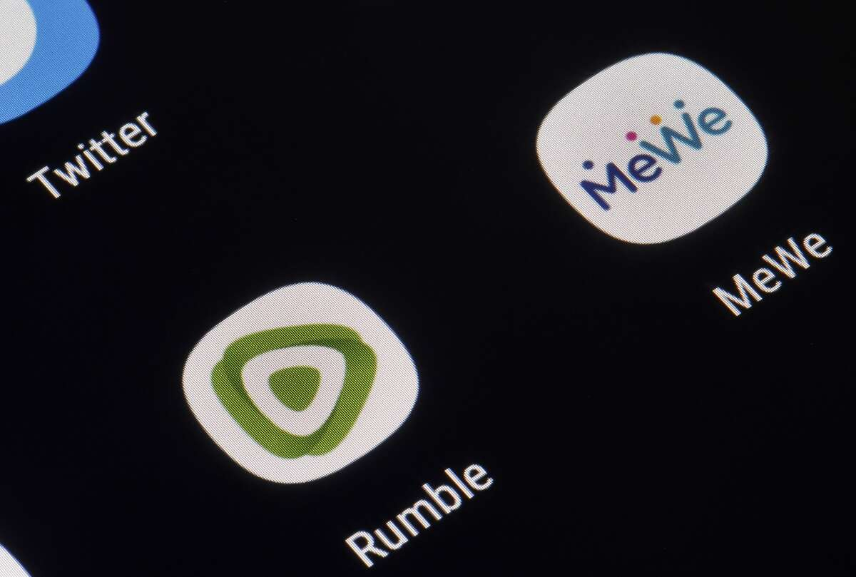 In this photo illustration, the logos of the social media applications Twitter, Rumble and MeWe are displayed on the screen of an iPhone.