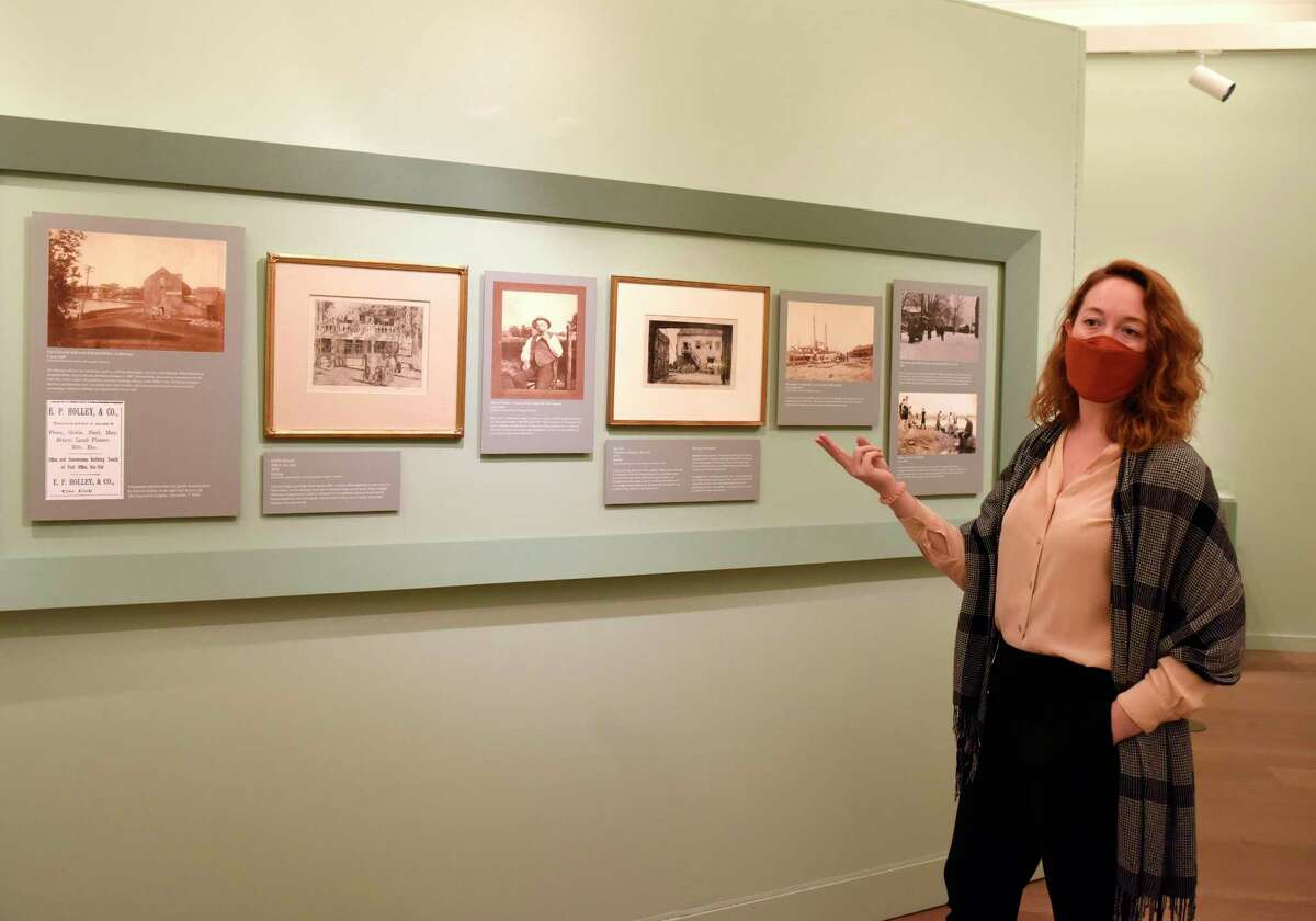 Curator of Exhibition and Collections Maggie Dimock shows old photographs of the neighborhood in which Childe Hassam's 1896 painting