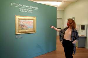 "Curator of Exhibition and Collections Maggie Dimock points out Childe Hassam's 1896 painting ""The Red Mill, Cos Cob"" at the new exhibit ""Lost Landscape Revealed: Childe Hassam and 'The Red Mill, Cos Cob'"" at the Greenwich Historical Society in the Cos Cob section of Greenwich, Conn. Monday, Jan. 11, 2021."