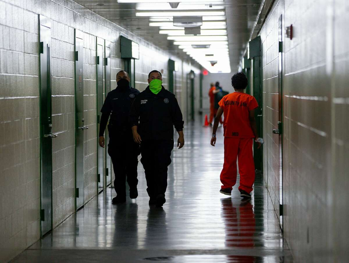 Harris County Sheriff's Office deputies walk past an inmate inside the detention facility on Thursday, Jan. 14, 2021, in Houston.