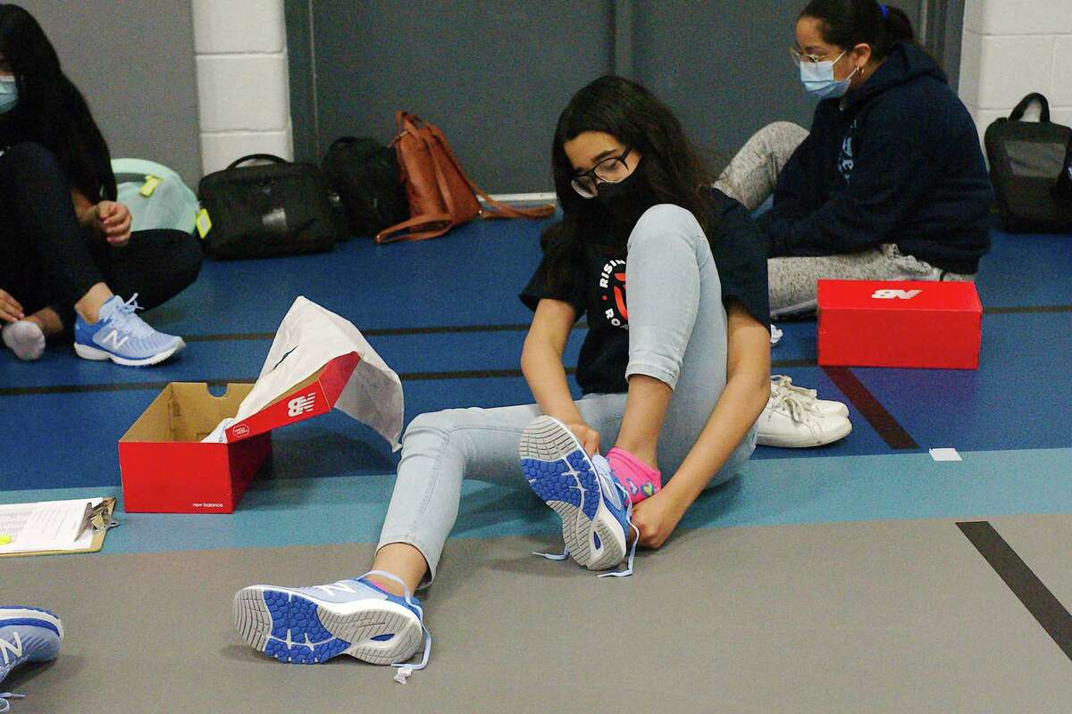 Milstead Middle School student Valeria Ocasio tries on a new pair of running shoes, one of over 800 pairs donated to the school's students through a partnership between the New Balance shoe company and New York Road Runners, a nonprofit organization that develops research-based movement activities and games as part of a physical education program.