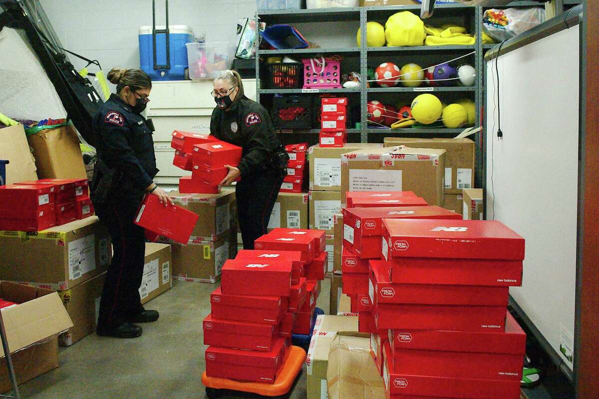 Pasadena ISD police officers Bianca Otero and Amber Murphy carry donated running shoes to the gym for distribution to students.