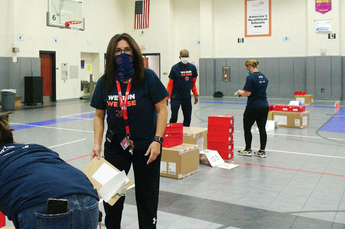 Milstead Middle School physical education teacher Deana Garza makes a last minute check as the school officials prepare to distribute the schools.