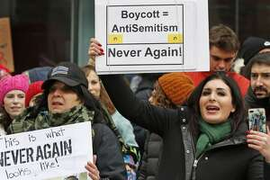 Political activist Laura Loomer, right, holds a sign across the street from a rally organized by Women's March NYC after she barged onto the stage interrupting Women's March NYC director Agunda Okeyo. Loomer was escorted off the stage after the incident.