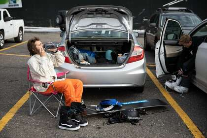 With the lodge closed to indoor dining due to Covid-19 precautions, snowboarder Noah Fischer of Santa Cruz eats his lunch in the parking lot on opening day at Heavenly Mountain Resort in South Lake Tahoe, California, November 20, 2020.