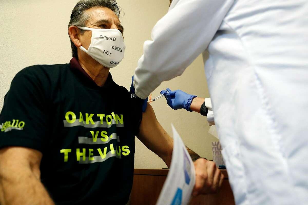 Nurse Practitioner Jerri Classen gives Oakland Councilman Noel Gallo the Moderna COVID-19 vaccine shot at Native American Health Center in Oakland, Calif., on Thursday, January 14, 2021.
