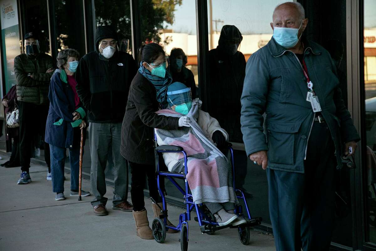 Loc To, 87, seated, waits with her daughter and other eligible people including Faraj Faraj, right, for their appointments to get the COVID-19 vaccine at the Alicia Trevino Lopez Senior Community One-Step Center, a WellMed senior center, in San Antonio on Monday, Jan. 11, 2021.