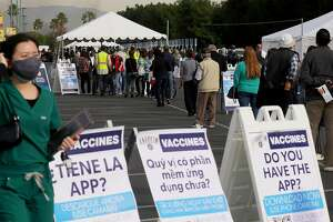 ANAHEIM, CALIFORNIA - JANUARY 13: People wait in line to receive the COVID-19 vaccine at a mass vaccination site in a parking lot for Disneyland Resort on January 13, 2021 in Anaheim, California. California announced that effective immediately, all residents 65 or older are eligible to receive the vaccine. (Photo by Mario Tama/Getty Images)