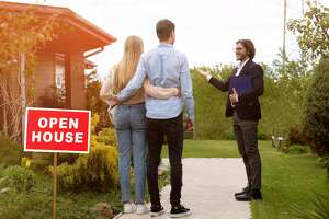 Confident real estate manager showing open house to young couple outdoors