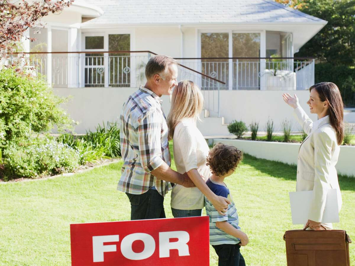 Family looking at the outside of a home for sale with a real estate agent.