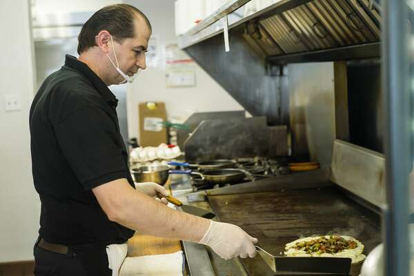 Lasko's cook Frank Shyti prepares an omelette for a customer Thursday, Jan. 14, 2021 at the restaurant, which is currently open for take-out from 7 a.m. to 3 p.m., just long enough to provide breakfast and lunch. (Katy Kildee/kkildee@mdn.net)
