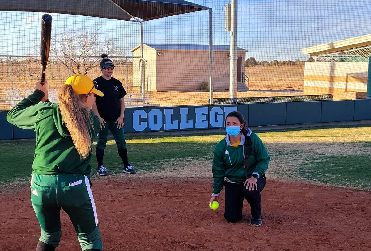 New Midland College softball coach Angel Castro, kneeling, is seen working with hitters during a recent practice.
