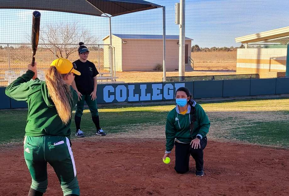 New Midland College softball coach Angel Castro, kneeling, is seen working with hitters during a recent practice. Photo: Forrest Allen/Midland College At