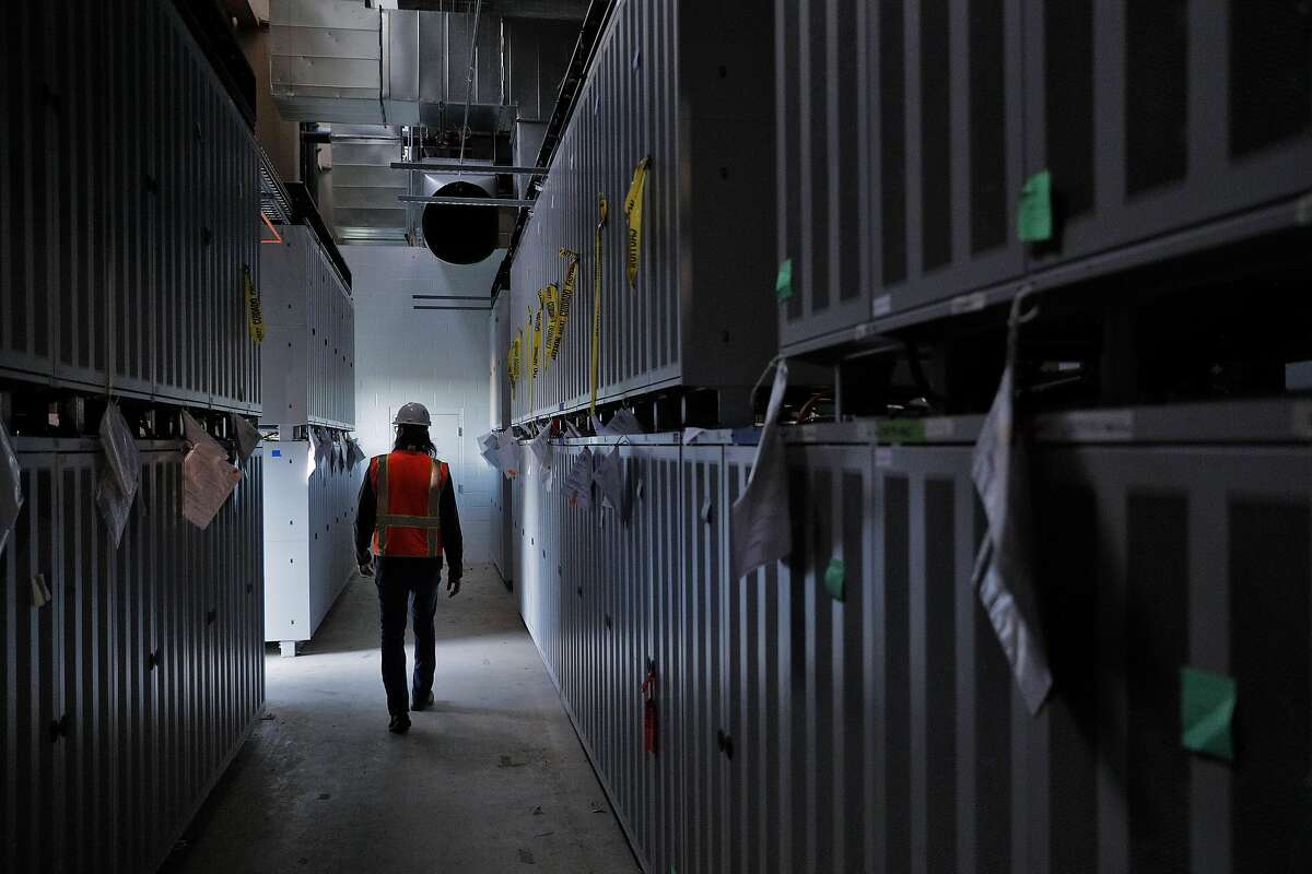 David Yeager, project manager for Vistra Zero, walks past cases containing storage batteries at the Moss Landing Power Plant.