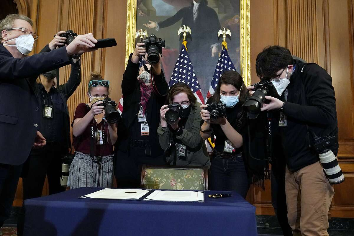 Photographers take pictures of the articles of impeachment Wednesday before House Speaker Nancy Pelosi signed it.