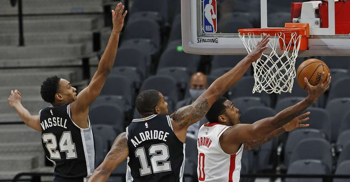 Sterling Brown #0 of the Houston Rockets drives past Dejounte Murray #5 of the San Antonio Spurs and Devin Vassell #24 at AT&T Center on January 14, 2021 in San Antonio, Texas. (Photo by Ronald Cortes/Getty Images)