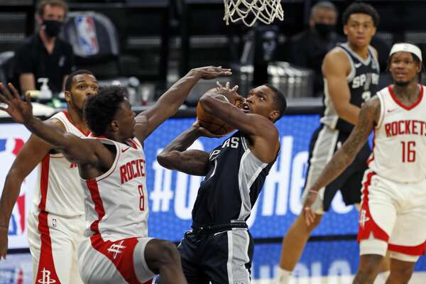 SAN ANTONIO, TX - JANUARY 14: Lonnie Walker #1 of the San Antonio Spurs drives past Jae'Sean Tate #8 of the Houston Rockets at AT&T Center on January 14, 2021 in San Antonio, Texas. NOTE TO USER: User expressly acknowledges and agrees that , by downloading and or using this photograph, User is consenting to the terms and conditions of the Getty Images License Agreement. (Photo by Ronald Cortes/Getty Images)
