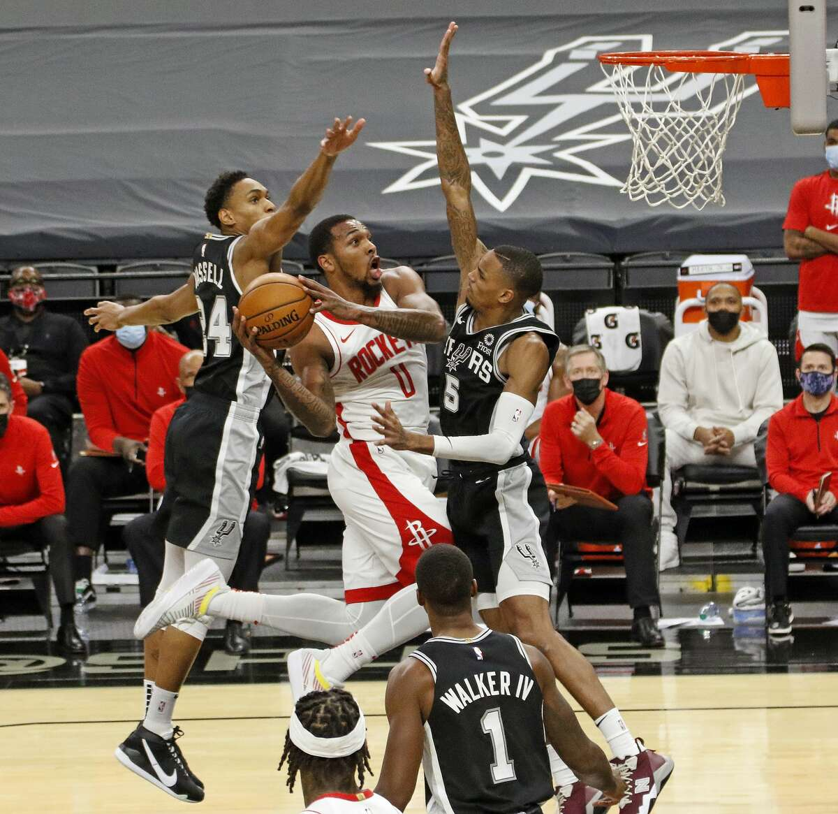 SAN ANTONIO, TX - JANUARY 14: Sterling Brown #0 of the Houston Rockets drives past Dejounte Murray #5 of the San Antonio Spurs and Devin Vassell #24 at AT&T Center on January 14, 2021 in San Antonio, Texas. (Photo by Ronald Cortes/Getty Images)