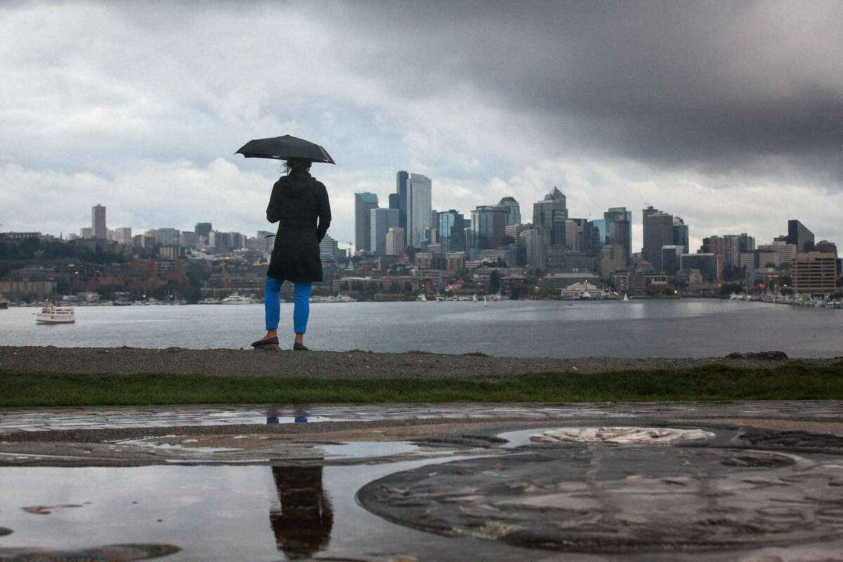 Woman holding an umbrella with Seattle in the background and rain clouds overhead.