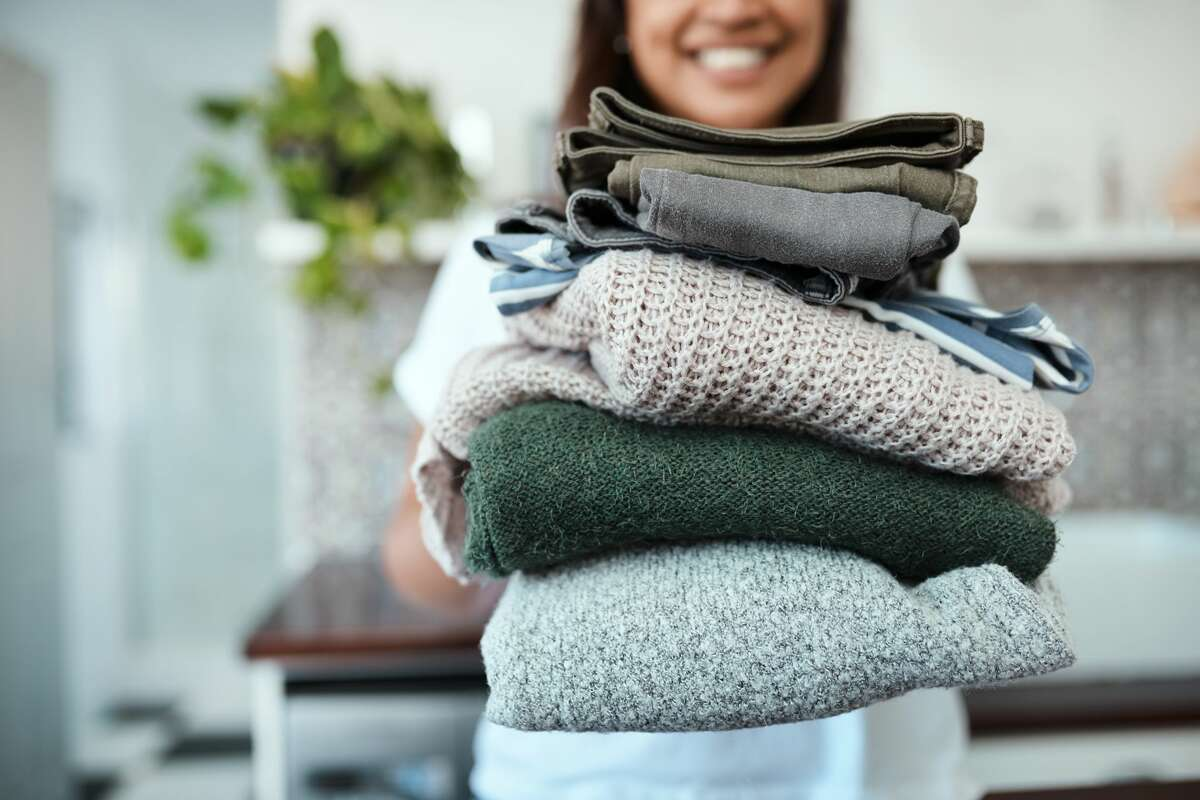 Closeup shot of a young woman holding a pile of folded laundry.