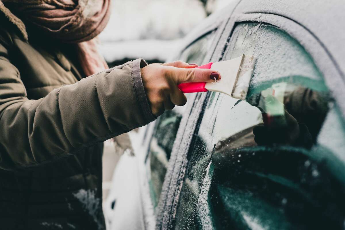 A person using an ice scraper on their car window.