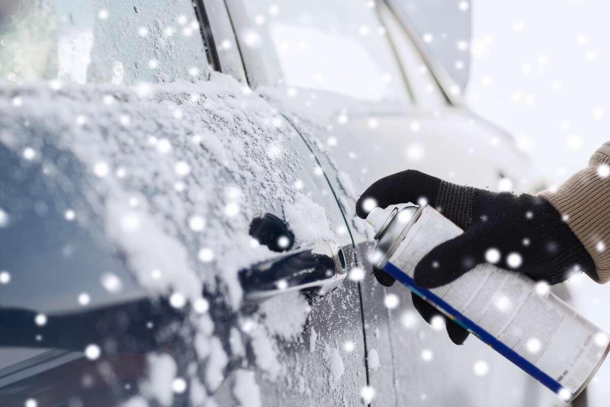 A closeup of a man using de-icer on his car lock.