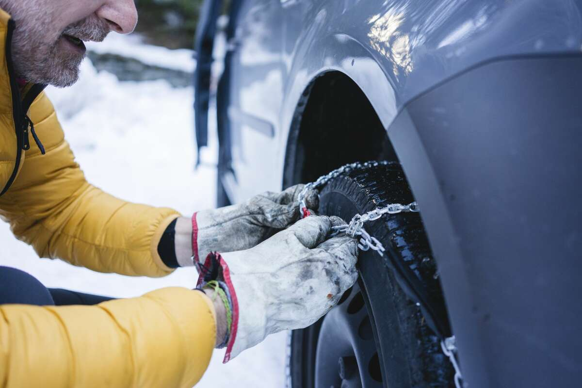 Man putting snow chains on his car.