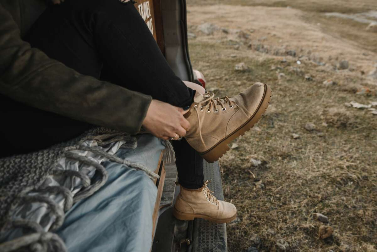 A young slender woman sits on the trunk of a van and puts on beige trekking boots.