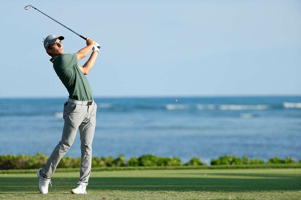 Joaquin Niemann follows his shot from the 17th tee in the Sony Open. He eagled No. 18 to claim a share of the first-round lead.