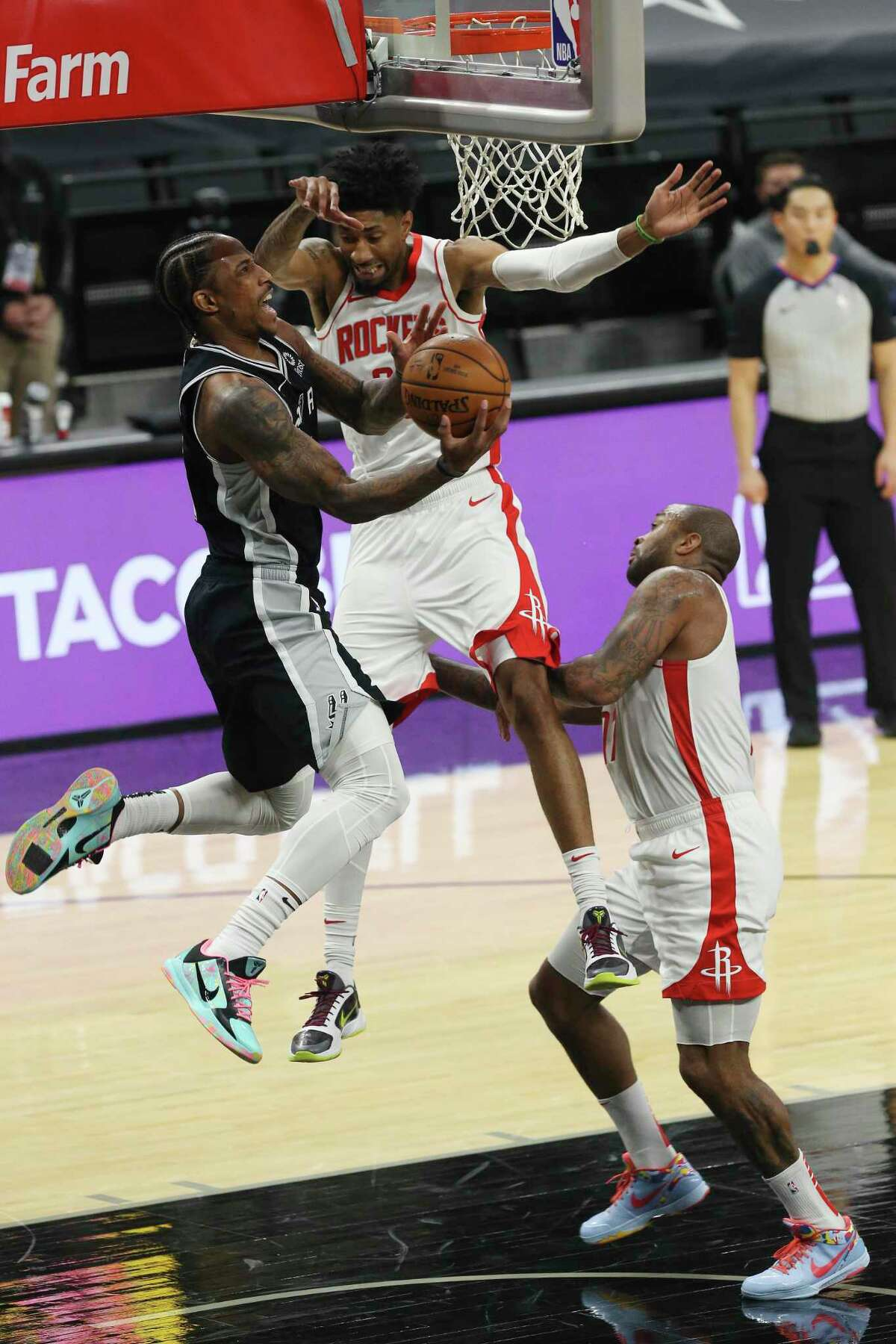 San Antonio Spurs' DeMar DeRozan goes under the basket as Houston Rockets' Christian Wood defends during the first quarter at the AT&T Center, Thursday, Jan. 14, 2021.