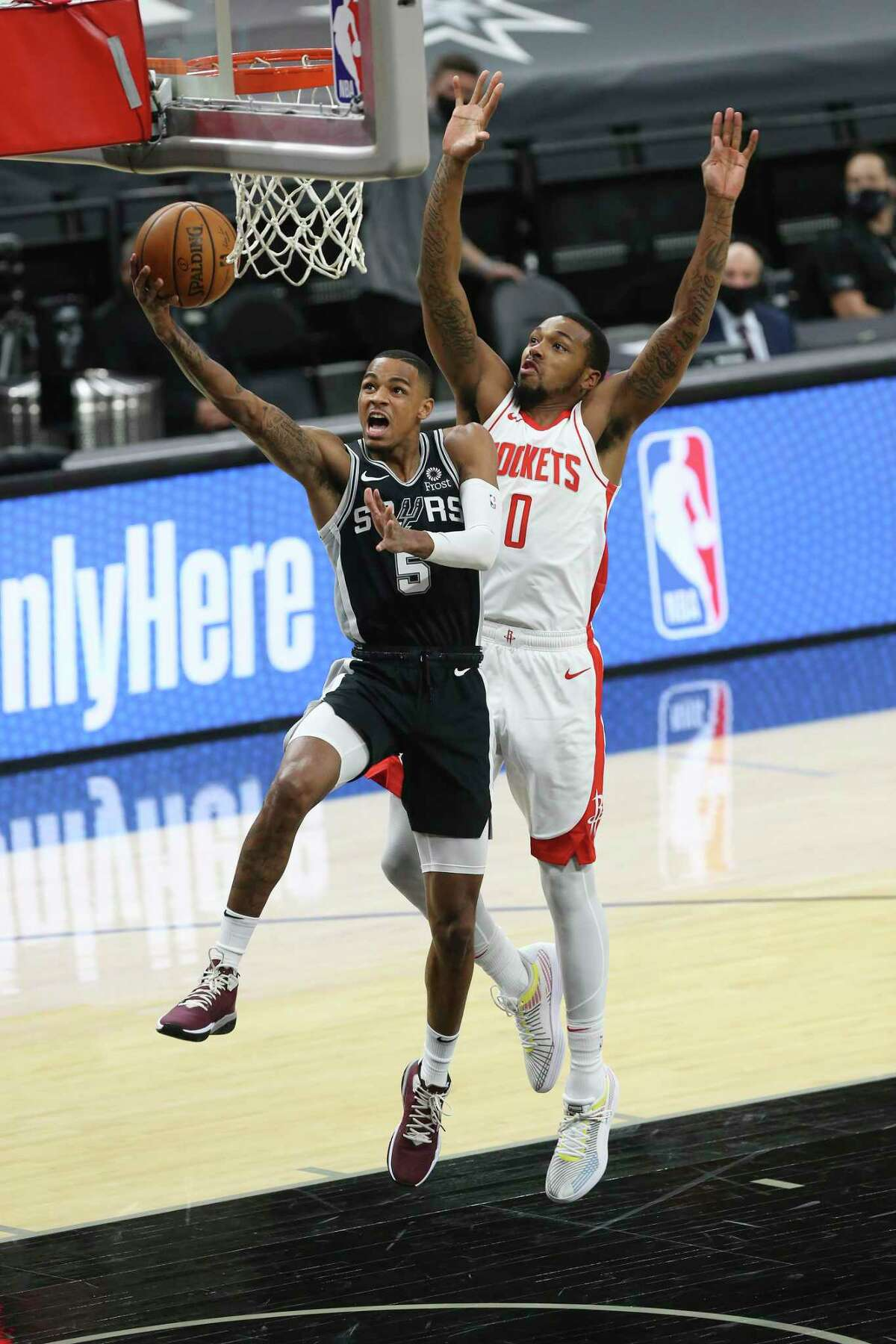 San Antonio Spurs' Dejounte Murray gets by Houston Rockets' Sterling Brown during the first quarter at the AT&T Center, Thursday, Jan. 14, 2021.