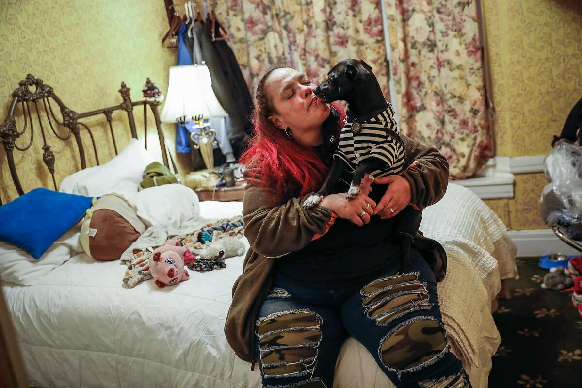 Chucky Torres embraces her dog Yoda in her hotel room in the Tenderloin on Wednesday, Dec. 16, 2020 in San Francisco, California. Chucky was previously homeless and hoping to get permanent housing.