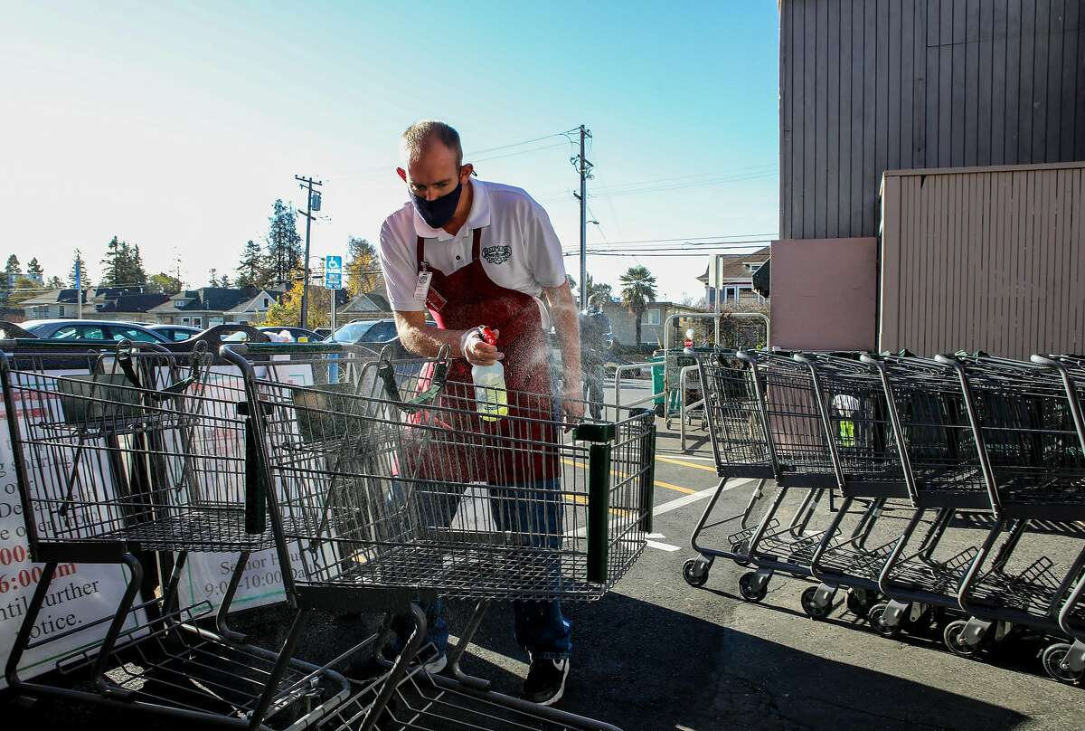 Associate James Obendorf sanitizes shopping carts at Piedmont Grocery in Oakland in December. Oakland and San Jose are considering mandating hazard pay for grocery workers during the pandemic.