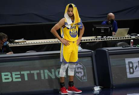 Golden State Warriors guard Stephen Curry waits at the scorer's table to take the floor in the first half of an NBA basketball game against the Denver Nuggets Thursday, Jan. 14, 2021, in Denver. (AP Photo/David Zalubowski)