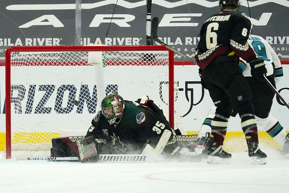 San Jose Sharks left wing Evander Kane, back right, scores a goal against Arizona Coyotes goaltender Darcy Kuemper (35) as Coyotes defenseman Jakob Chychrun (6) watches during the third period of an NHL hockey game Thursday, Jan. 14, 2021, in Glendale, Ariz. The Sharks won 4-3 in a shootout. (AP Photo/Ross D. Franklin)