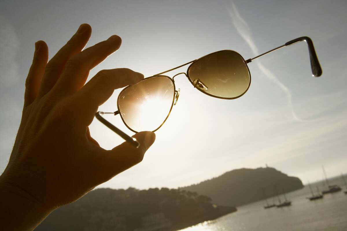 A hand holding aviator sunglasses up against the sky.