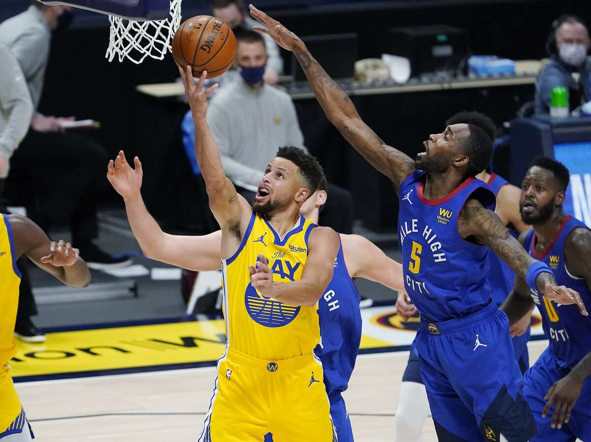 Golden State Warriors guard Stephen Curry shoots next to Denver Nuggets center Nikola Jokic, back, and forward Will Barton during the second half of an NBA basketball game Thursday, Jan. 14, 2021, in Denver. The Nuggets won 114-104. (AP Photo/David Zalubowski)