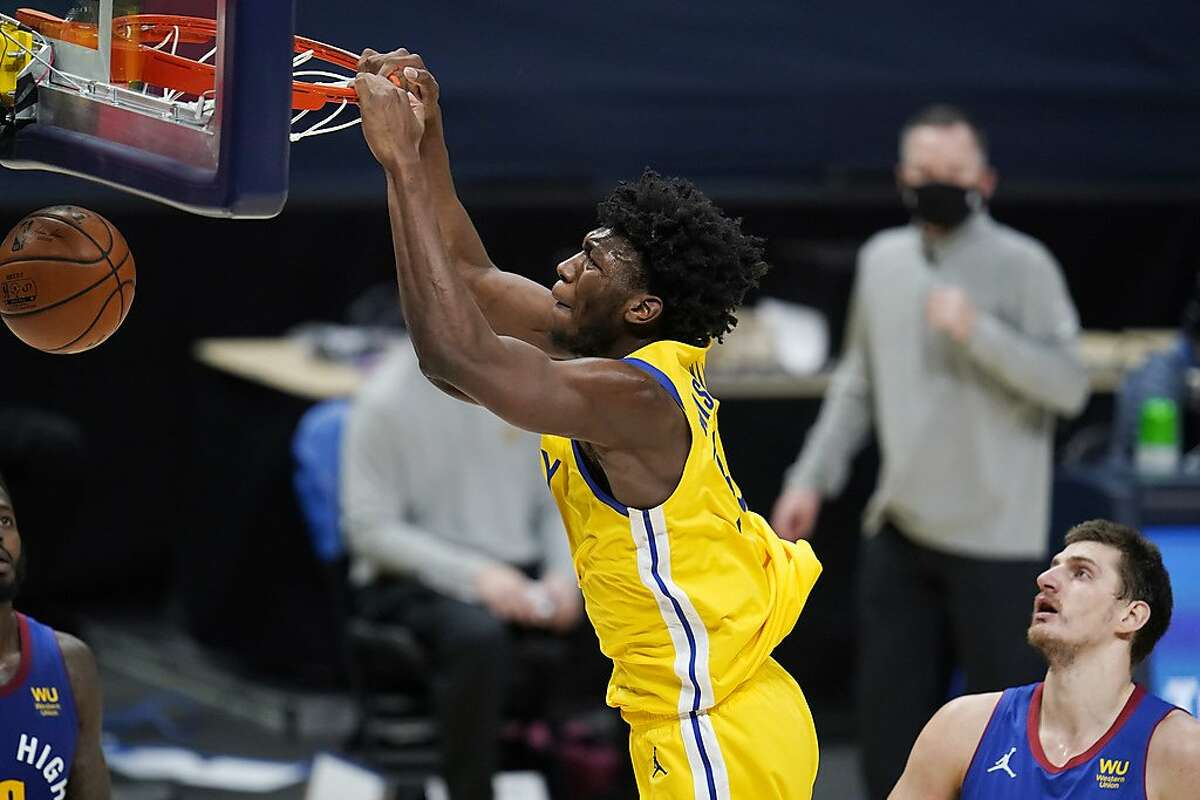Golden State Warriors center James Wiseman hangs from the rim after a dunk, next to Denver Nuggets center Nikola Jokic during the second half of an NBA basketball game Thursday, Jan. 14, 2021, in Denver. The Nuggets won 114-104. (AP Photo/David Zalubowski)