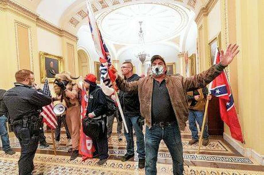 Supporters of President Donald Trump are confronted Jan. 6 by U.S. Capitol Police officers outside the Senate Chamber inside the Capitol in Washington. Both within and outside the walls of the Capitol, banners and symbols of white supremacy and anti-government extremism were displayed as an insurrectionist mob swarmed the U.S. Capitol. Photo: Manuel Balce Ceneta   Associated Press
