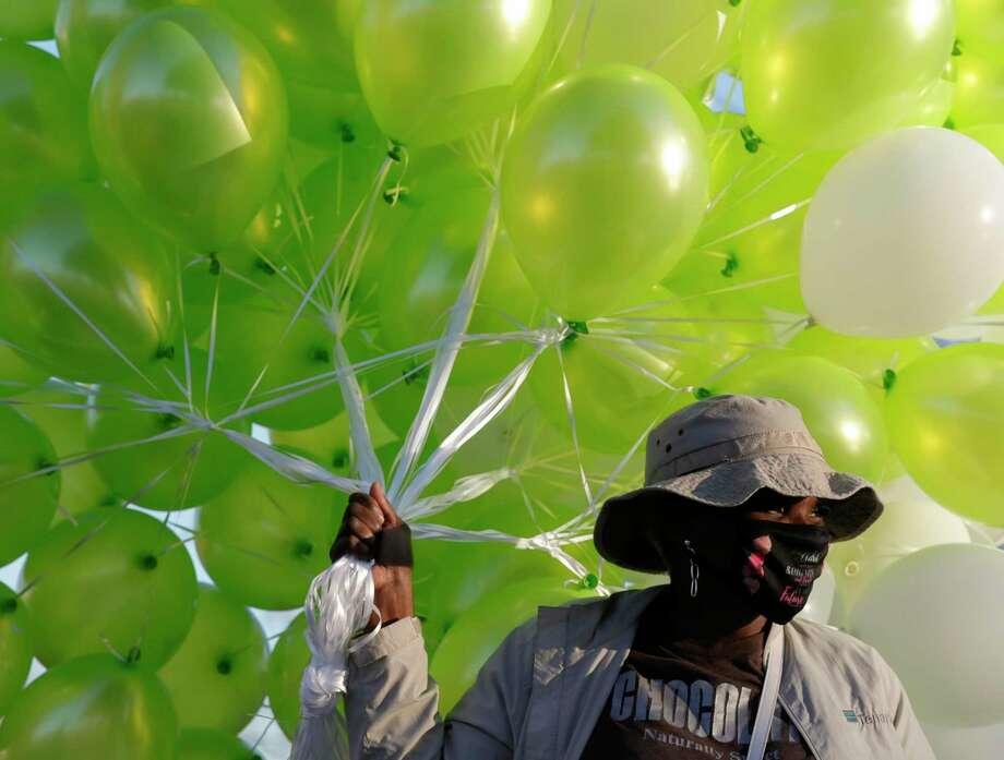 Kimberly Griffin holds a group of balloons as family and friends of Shantrell Goodnight gather to release 200 lime green and white balloons to commemorate her 24th birthday at MLK Park, Thursday, Jan. 14, 2021, in Willis. Goodnight was struck and killed by another vehicle on Interstate 45 while standing along the freeway south of FM 1097 after walking out of her boyfriend's disabled Nissan Rouge on Jan. 9. Photo: Jason Fochtman, Houston Chronicle / Staff Photographer / 2021 © Houston Chronicle