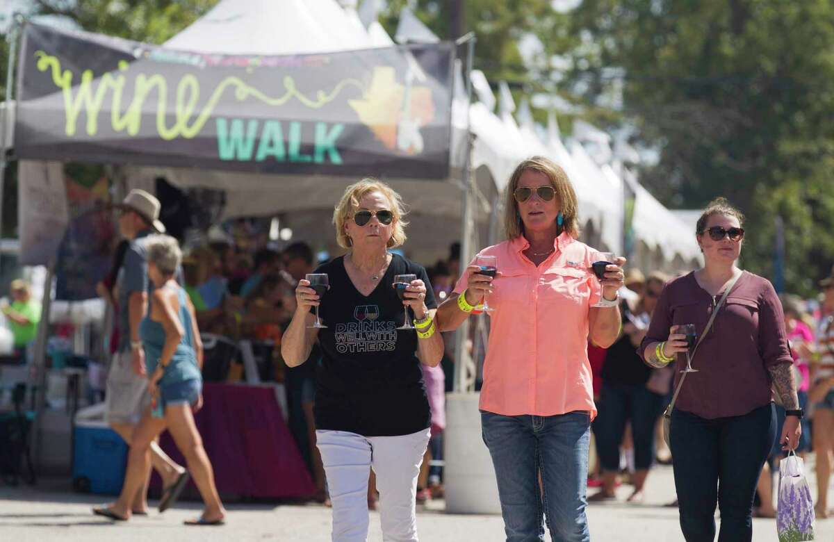 Paula Taggard and Cindy Fitt walk with wine glasses in hand during the annual Montgomery Wine and Music Festival, Saturday, Sept. 21, 2019, in Montgomery. This year's event is Saturday and marks a return to the in-person event in downtown historic Montgomery.