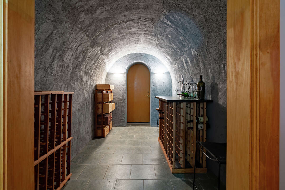 """Cave-like, climate-controlled wine cellar and tasting area at 10 Nature Lane, Shelton, accommodating 500 bottles. Homeowners can do more than just watch the activity on the river. This house is within walking distance to Southbank Park on River Road, which """"has become a popular destination for fishing, kayaking, and picnicking along the Housatonic River ... A suggested canoe/kayak trip is from the Derby boat launch to Southbank Park,"""" according to the Shelton Conservation Commission."""