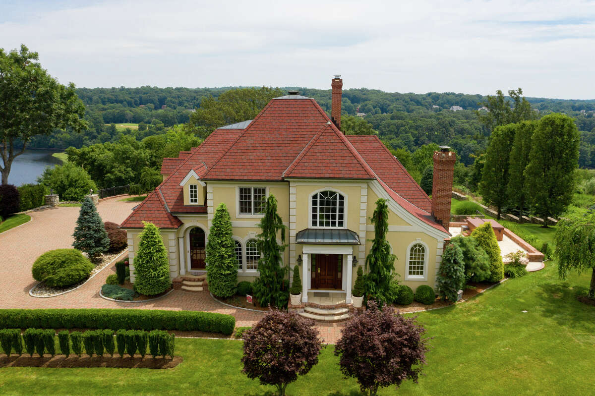 """The Mediterranean-style colonial at 10 Nature Lane, Shelton, overlooking the Housatonic River. This 6,778-square-foot Energy Star-rated house with geothermal heat was built in 2001 on a 1.74-acre parcel high above River Road (Route 110) on a cul-de-sac in """"an exclusive neighborhood of only eight homes, all overlooking the river,"""" said Listing Agent Eric Schuell. """"The best views are in summer with all the boats going up and down the river,"""" he said."""