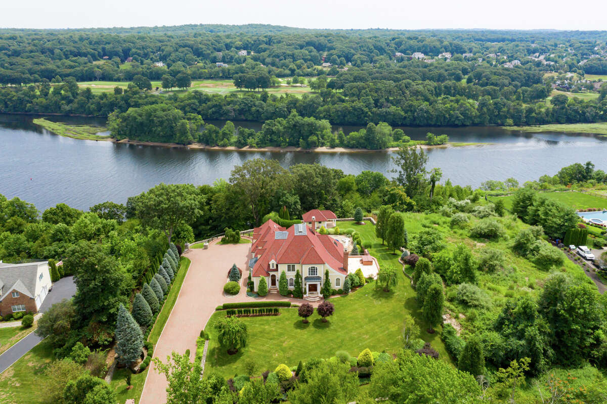 """A 1.74-acre parcel at 10 Nature Lane, Shelton looking over the Housatonic River. """"There's a reason why they call it Nature Lane. As soon as you arrive, a sense of peace and tranquility encircle this impeccable, private, villa-like home,"""" Schuell said. This house is opulent yet casual. Outside, the professionally-landscaped property has an in-ground swimming pool and cabana, paving stone terraces, a large upper deck and """"a covered area for entertaining even in the rain"""" equipped with a television hook-up, Schuell said."""