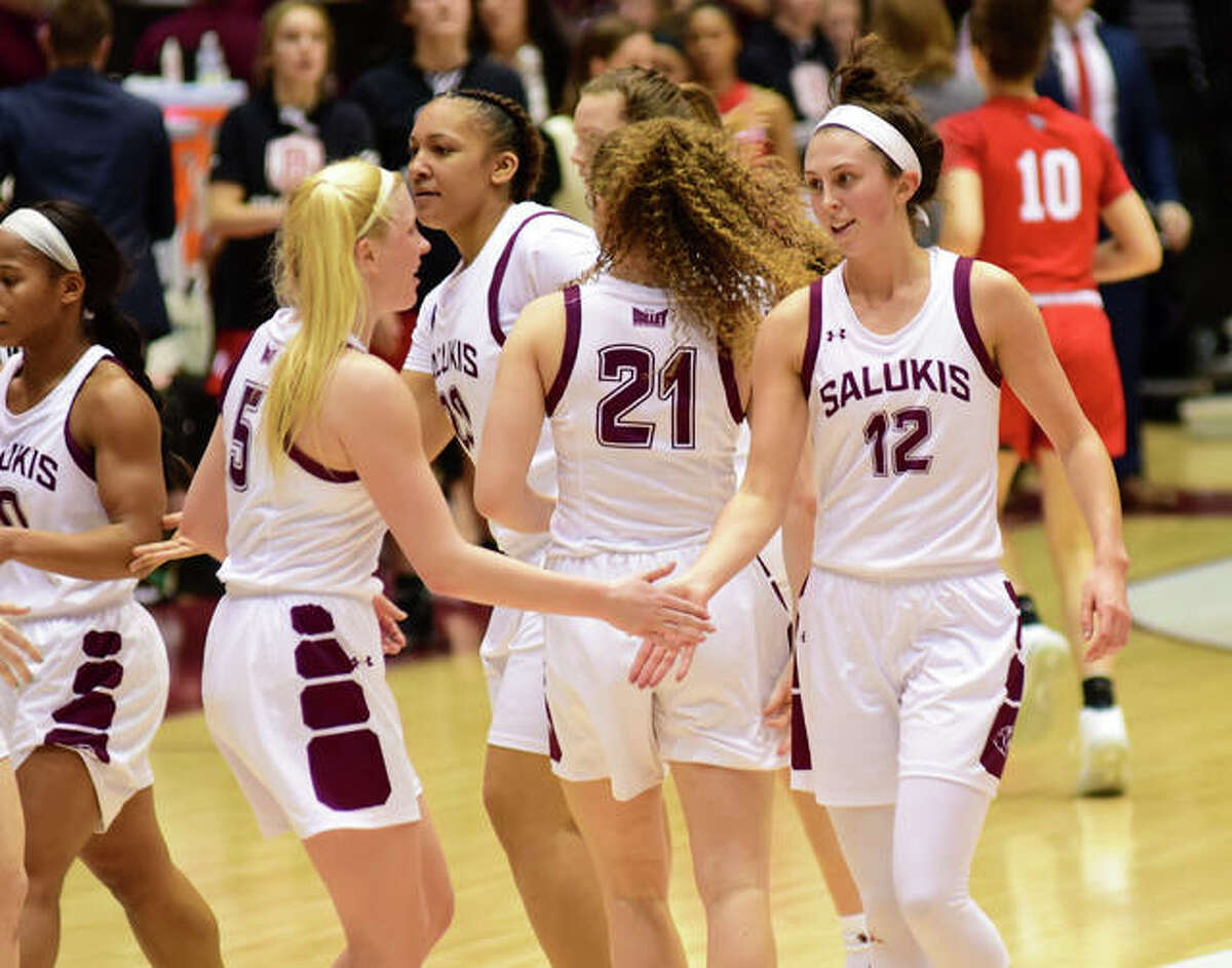 SIUC guard Makenzie Silvey is congratulated by a teammate at the bench during a timeout.